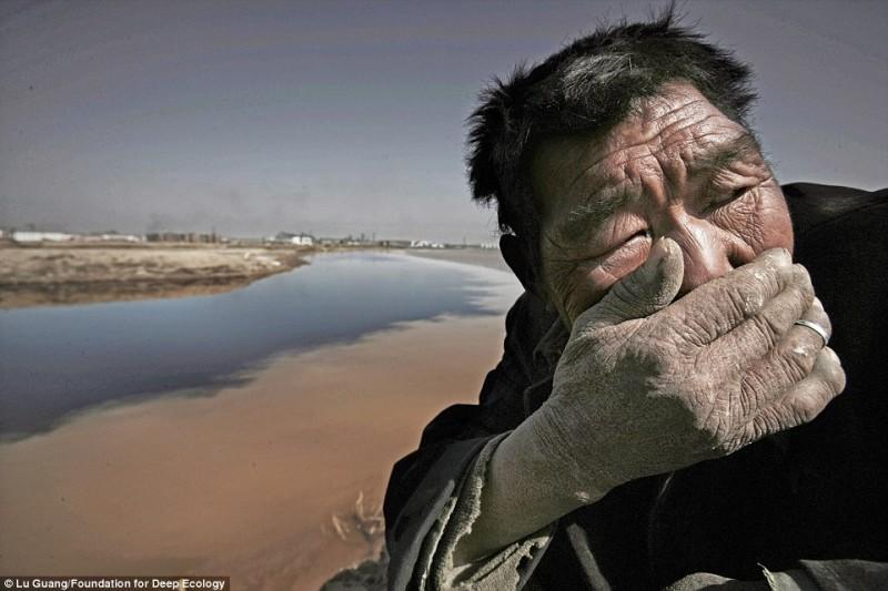 Un contadino si copre la bocca e il naso: impossibile sopportare la puzza del Fiume Giallo in Mongolia
