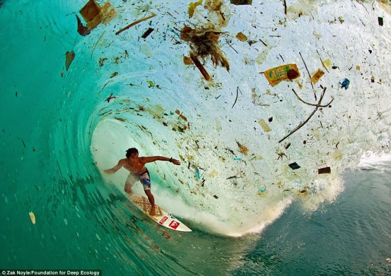 Il surfista indonesiano Dede Surinaya cavalca un'onda di sporcizia e rifiuti (Java, Indonesia)